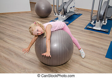 girl exercising with fit ball - little blond girl feeling...
