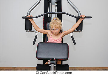 little child in the gym - adorable little blond girl working...