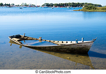 scuttled boat - little wooden scuttled boat in the sea