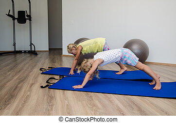 girls doing exercise - two little blond girls in gym with...