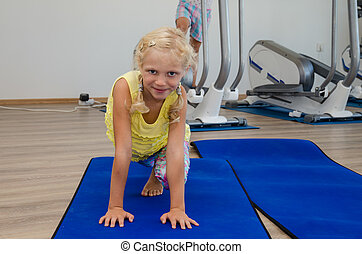 girl in the gym - little blond girl in gym doing exercise in...