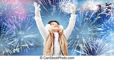 happy little girl wearing earmuffs over firework - winter,...