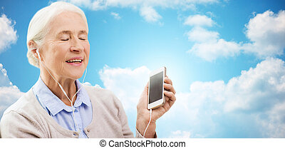 senior woman with smartphone and earphones at home