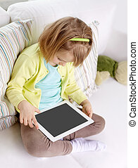 little girl with tablet computer at home