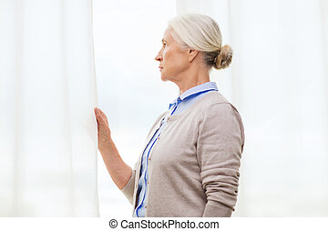 lonely senior woman looking through window at home
