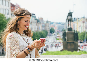 Longhaired bohemian young lady writing sms on mobile, Prague...