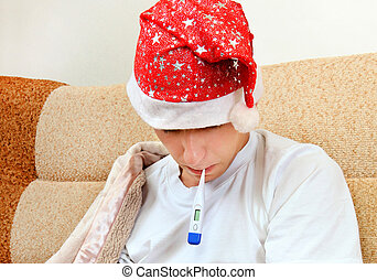Sick Young Man with Thermometer - Sick Teenager in Santa Hat...