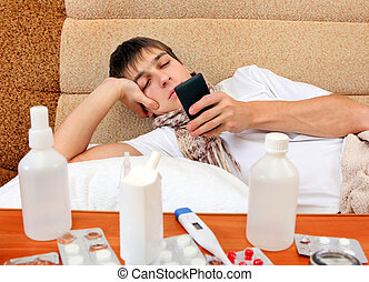 Sick Young Man with the Phone on the Sofa at the Home