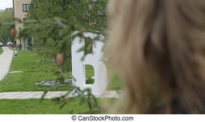Woman looking to letter B due to tree