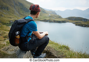 Teenage hiker by the lake in the mountains