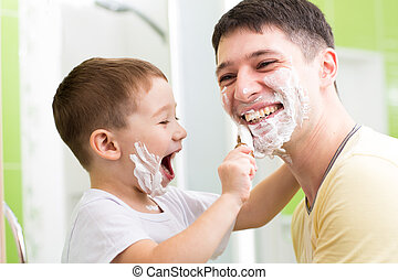 Father and his kid son playing in bathroom Child boy putting...
