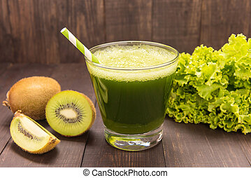 Healthy green smoothie with kiwi, lettuce on rustic wood background