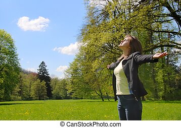 Woman enjoys sun in spring time outdoors - Woman is enjoying...