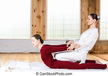 Woman getting thai stretching massage - Young woman getting...