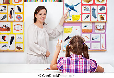 Young girl in elementary science class raising hand