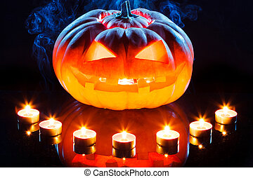 Halloween pumpkin with scary face and burning candle on...