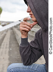 Young man in depression smoking a cigarette on a stadion...