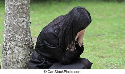 Depressed woman near the tree