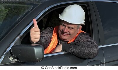 Worker in car showing thumb up