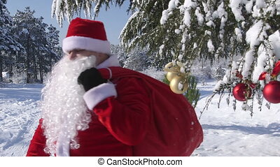 Santa Claus with gift bag walking through snow covered winter forest
