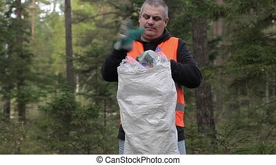 Man with bag of plastic bottles in forest