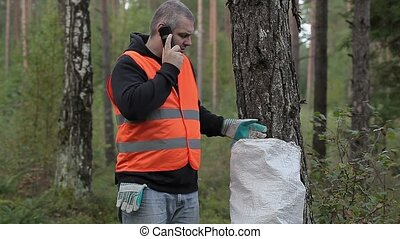 Man with cell phone and bag of plastic bottles in forest