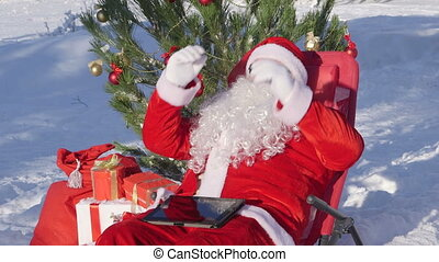 Santa Claus near Christmas tree in snow covered winter forestt