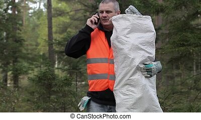 Man with cell phone and bag of plastic bottles