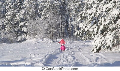 Mother pulling child on sled through snow in winter forest