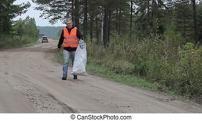 Man with cell phone and bag of plastic bottles on the road...