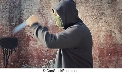 Man with knife dressed in mask near the wall