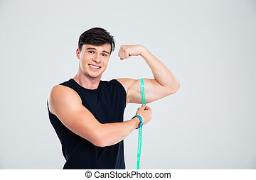 Portrait of a happy fitness man measuring his biceps...