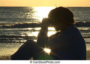 Prayer On The Beach - Mature woman sits on the beach praying...