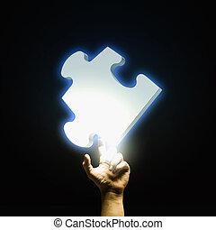 Puzzle element - Human hand pointing with finger at puzzle...