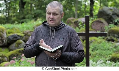 Preacher with Bible and rosary at outdoors church near cross...