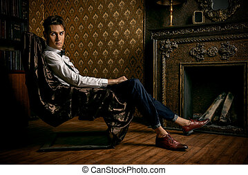 by the fireplace - Elegant handsome young man sitting by the...