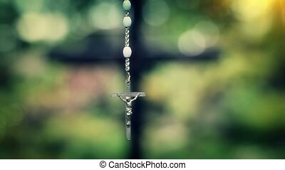 Rosary slowly swinging on green background