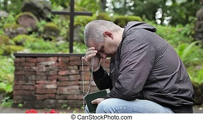 Man with Bible and rosary praying at outdoors church near...