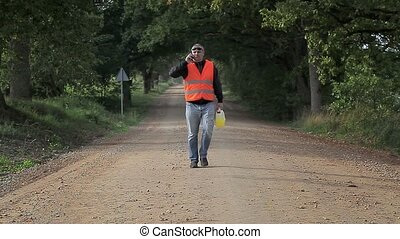 Man with plastic can on rural road