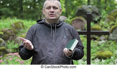 Preacher with Bible and rosary at outdoors church