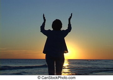 Raised Hands - Mature woman at the beach at sunset with her...