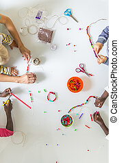 Children doing bead work - Overhead view of four children,...