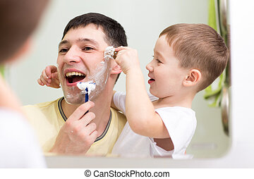 child boy and his father shave looking at mirror in bathroom...