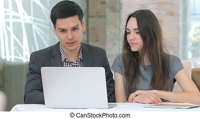 Young attractive business man and woman discussing comparing...