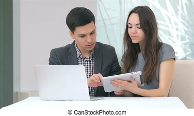 Young attractive business man and woman discussing collating...
