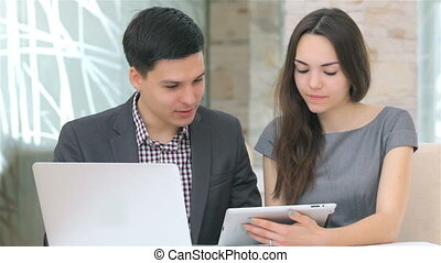 Young business man and woman discussing collating data on the tablet