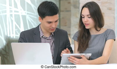 Man and woman discussing collating data on the tablet -...