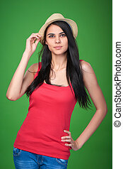 Teen girl wearing straw hat looking up in thoughts, studio...