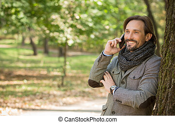 Handsome middle-aged man talking over mobile phone in the...