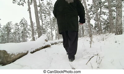 Lost elderly woman walks in snow through the woods or park in winter